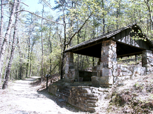 early spring scene of graveled trail on the left and stone trail shelter on the right.