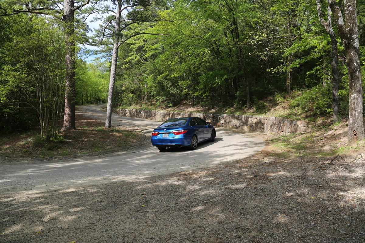 A blue Honda Civic drives up the forested winding road on Hot Springs Mountain Drive.