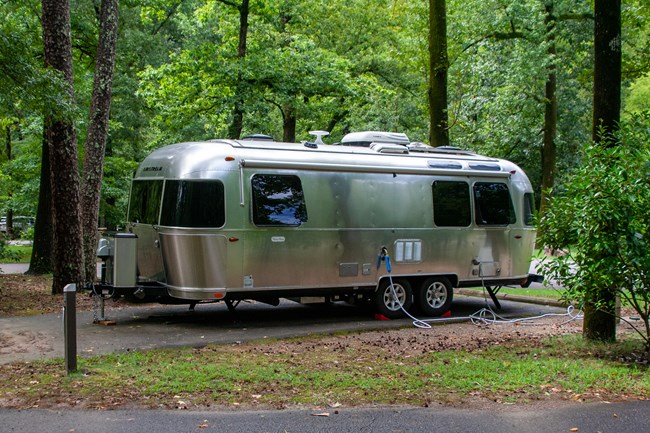 A Silver Airstream camper parked in Gulpha Gorge Campground under a green canopy of trees