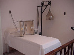 The men's massage room with a narrow bed covered with a white sheet,