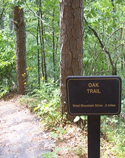 color photo of Oak Trail trail sign, sign is made of dark brown metal with gold lettering