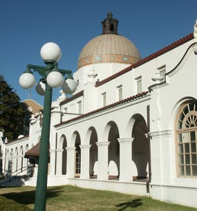 Photo of Quapaw Bathhouse from south end, showing front of building. Building is white stucco, Spanish revival style architecture and has a large mosaic dome in center of building