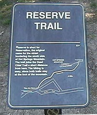 color photo of Reserve Trail trailhead sign. Sign is made of dark brown metal with gold lettering and map of trail
