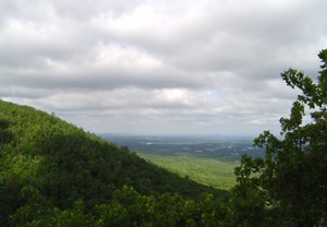 beautiful view from West Mountain showing portion of hillside on the left, trees on the right, with a gray overcast sky and green valley below