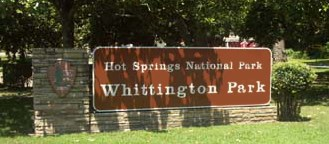 color photo of Whittington Park sign, redwood colored with white lettering, mounted on stone base with NPS arrowhead on left