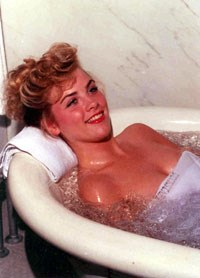 Large ceramic white bath tub, typical of those in the traditional bathhouses, with a large faucet on the left and a grab bar on the gray marble wall behind the tub;blond haired woman in the tub