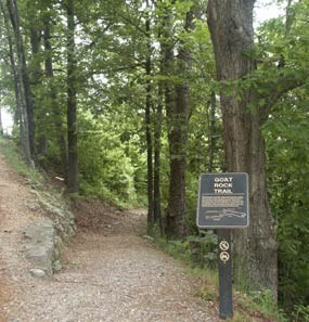 Goat Rock Trail trailhead with trail in center and trail sign on right; trail is flanked by trees.
