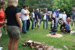 Group of visitors watch living historian start fire with a bow.