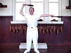 Man standing in old gymnasium in white undershirt and white pants with an Indian club in each hand.