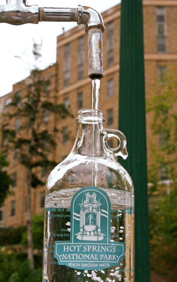 A glass bottle with the Hot Springs National Park logo on it is filled by thermal water at one of the fountains.
