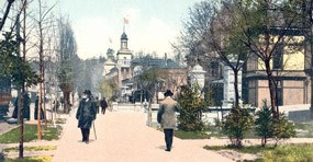 Tinted post card of Bathhouse Row in 1908 in the winter. Gentlemen stroll in front of the Palace Bathhouse with the Maurice Bathhouse on the right and the Arlington Hotel visible in the background. On left side of the sidewalk are the slender bare trunks of the Lombardy poplars with some Southern magnolia greenery visible, and on the right side are bare young elm tree trunks.