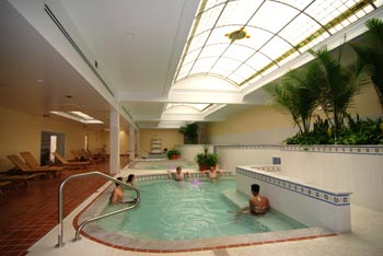 Interior shot of long narrow pool from one end, with terra cotta colored floor tile on left and stained and clear glass skylight above on right.
