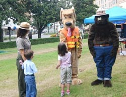 Female ranger, young boy and girl look at Bobber dog mascot with a life jacket on and Smokey Bear