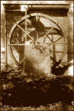 sepia tone photo of end of stone building with metal water wheel attached to it