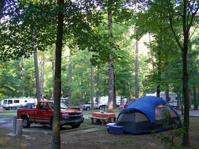 Blue dome tent in foreground with red pickup truck parked at campsite. In background you can see RV campers. All with trees surrounding.