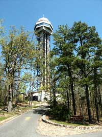 Color photo of steel tower, looking from driveway below tower, spring season with trees half leafed out.