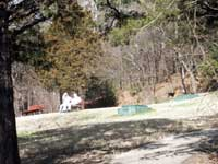 spring scene of grassy hillside with cement trail on lower right and two green boxes sticking up from ground to left of trail, visitors sitting on a wooden park bench in front of a cedar tree on far left, with wooded hillside in background