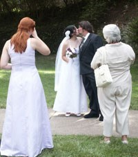 bride and groom kiss as bridesmaid and woman look on