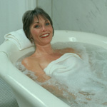 Smiling woman in ceramic tub with water; woman is draped with a white towel