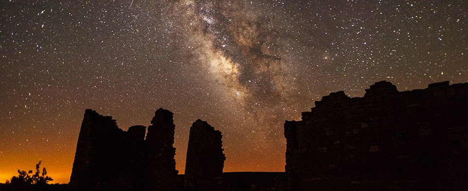 The Milky Way arcs above a silhouetted rock structure