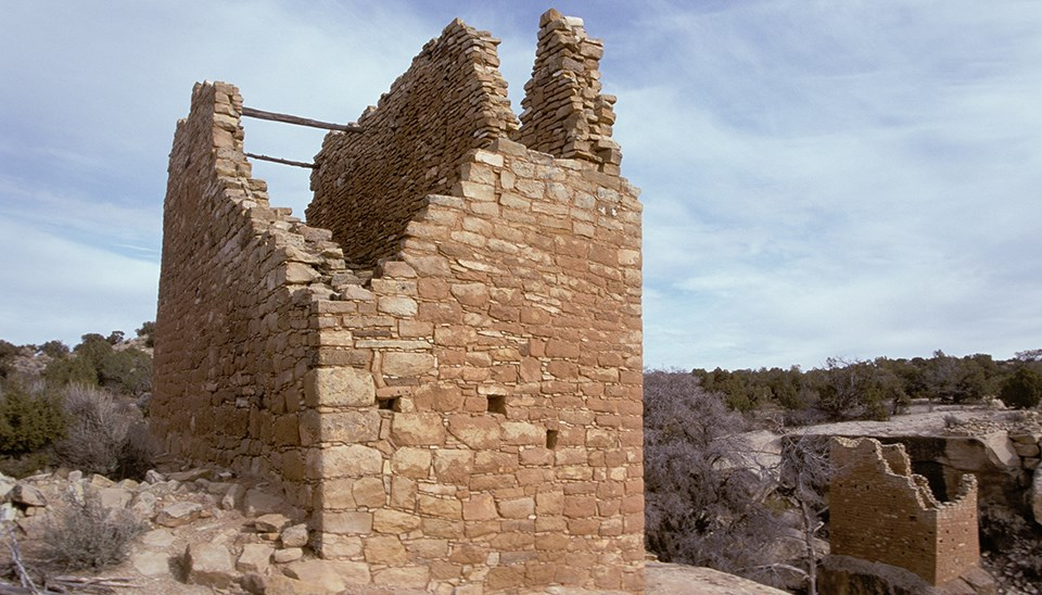 a stone tower with wood cross beams