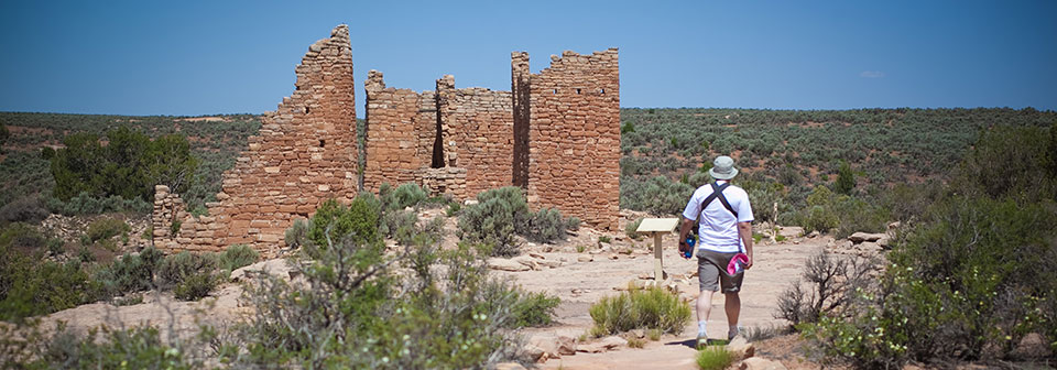 a man walks toward a cliff dwelling