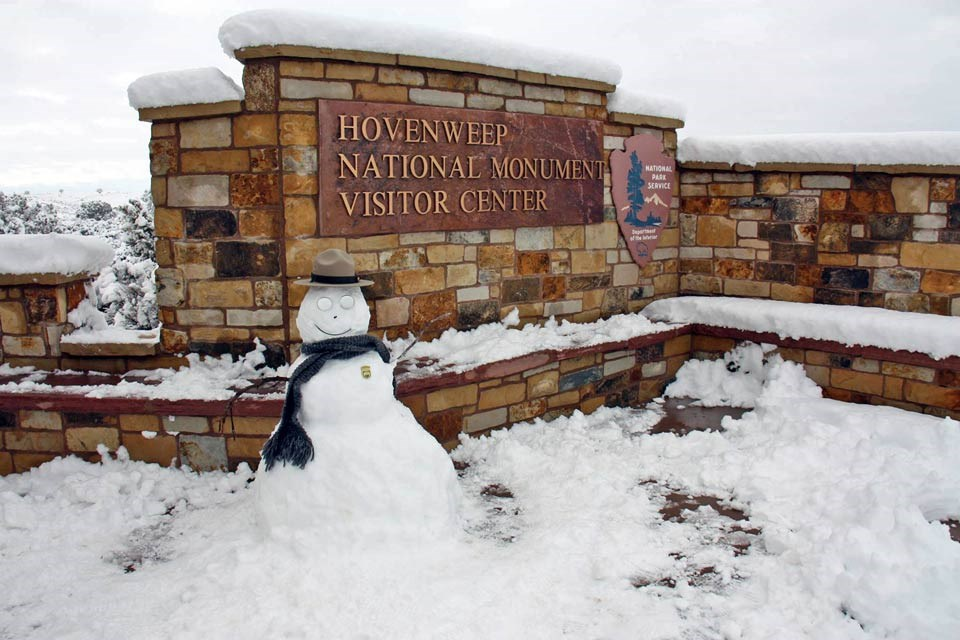 snowman decorated as a park ranger in front of the visitor center sign