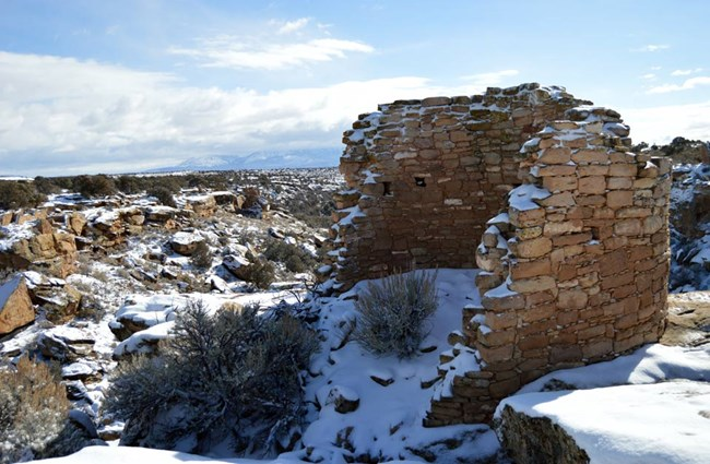 tower point ruin covered in snow with canyon and Sleeping Ute mountain in the background