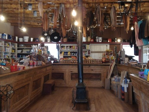Interior of a historic trading post general store. There are wooden counters on three sides of the room with a cast iron stove in the center. a variety of foodstuffs and mercantile items are behind the counters.