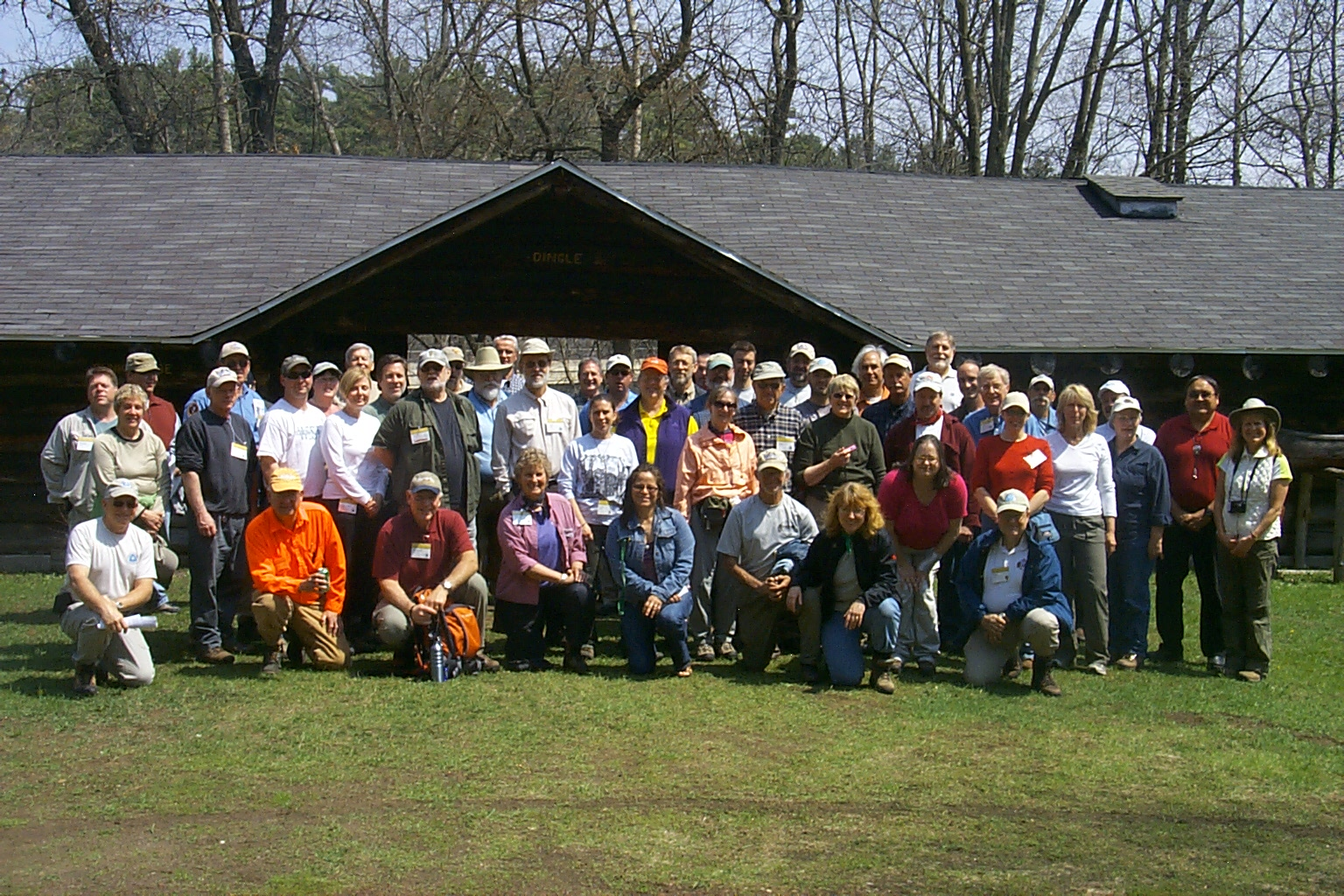 Participants gather fror a group photo in front of a building at the Menominee Logging Museum.