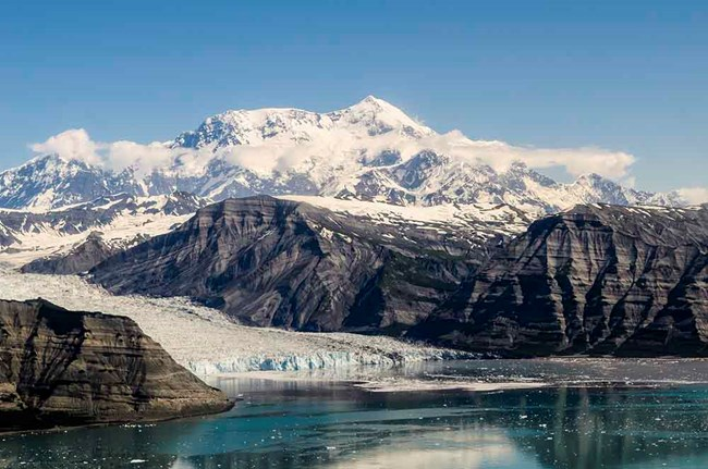 A panorama of the Chugach Mountains with a tidewater glacier and Mt St Ellias in the background.