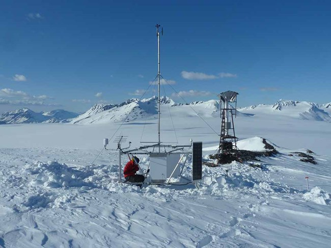 A researcher collects winter data from the weather station.