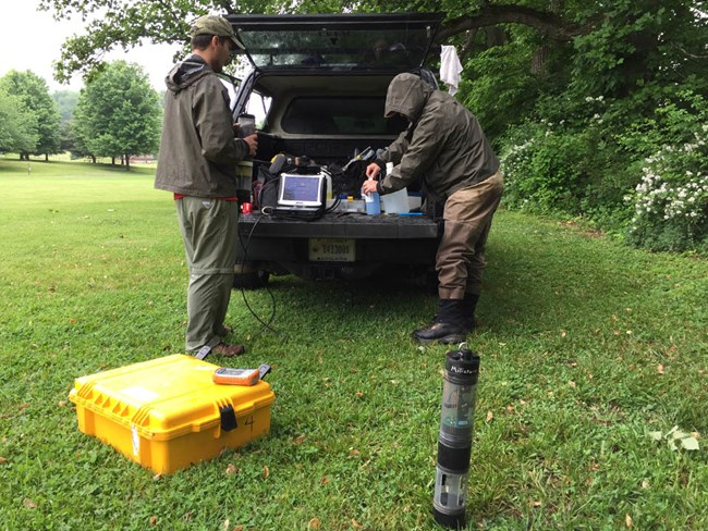 Two scientists removing water quality monitoring devices from the back of a vehicle parked at a field site.