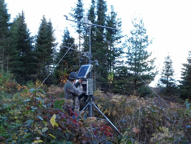 Scientist checks instruments at a remote weather station