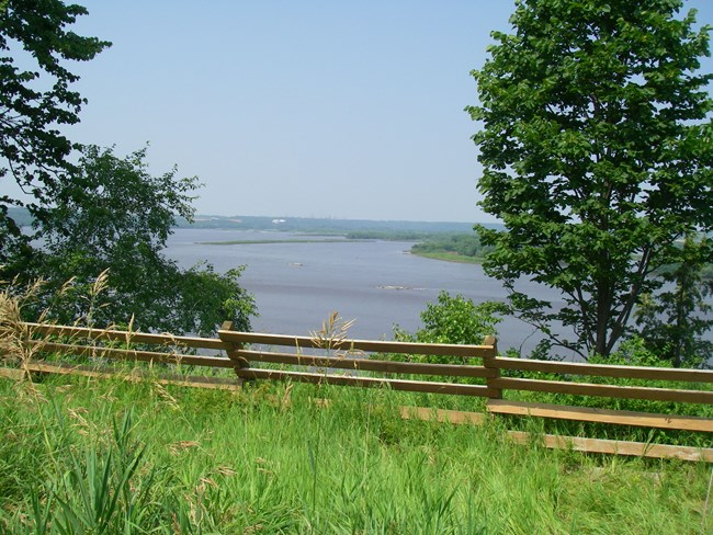 A view of the river beyond a fence line on a bluff