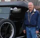 David G. Peitz alongside an antique vehicle