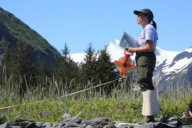 NPS employee holding a measuring tape and notes; snowy mountains in the background