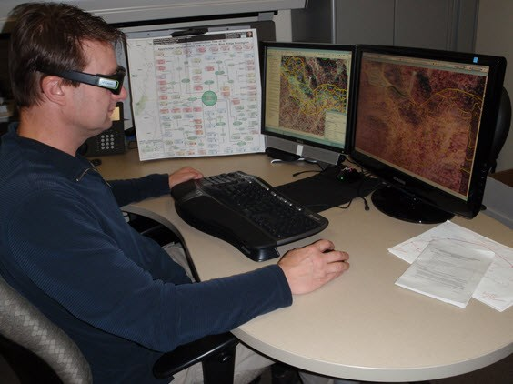 Technician in front of computer monitors using 3-D glasses to view maps