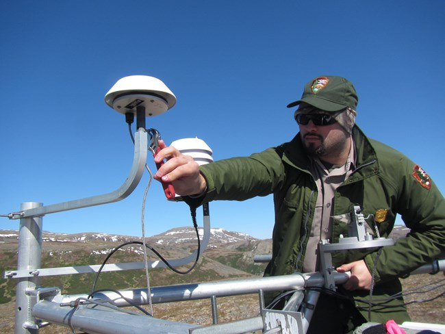Park employee in a remote area fixing a weather station