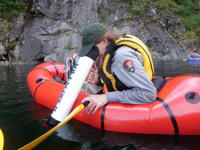 National Park Service scientist in a raft using a scope to see under water