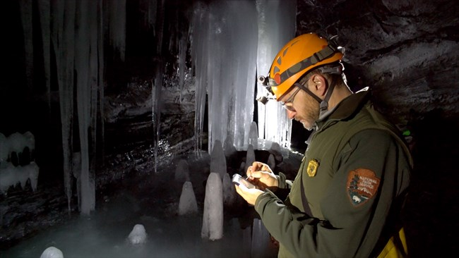 Field technician inside a cave entering data on hand held device with ice in background