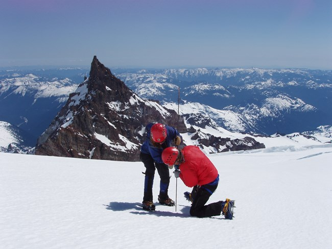 Two people in winter clothing probing a glacier to measure snow depth with snowy peaks in background