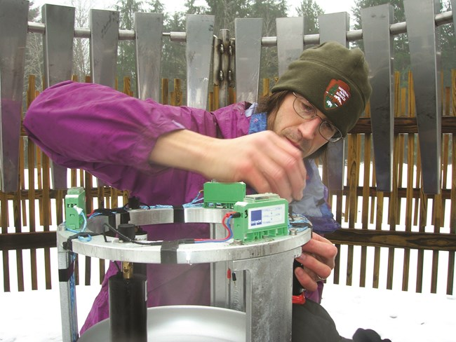 Researcher servicing a SNOTEL weather station in winter