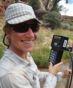 Woman with water quality meter smiles at camera