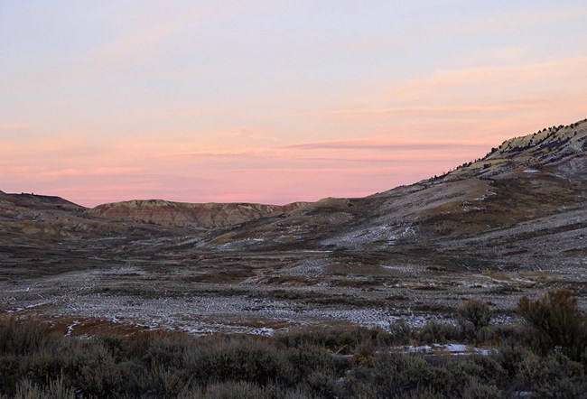 Pink sky over eroded landscape dusted with snow