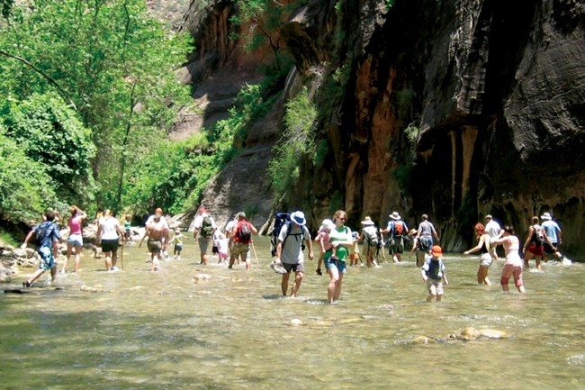 Crowd of people wades in shallow river between canyon walls.