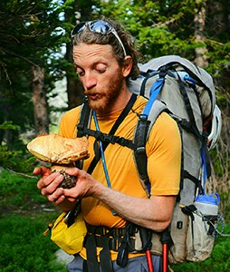 Man wearing backpack looking at large mushroom