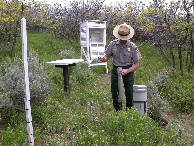NPS employee at climate monitoring station