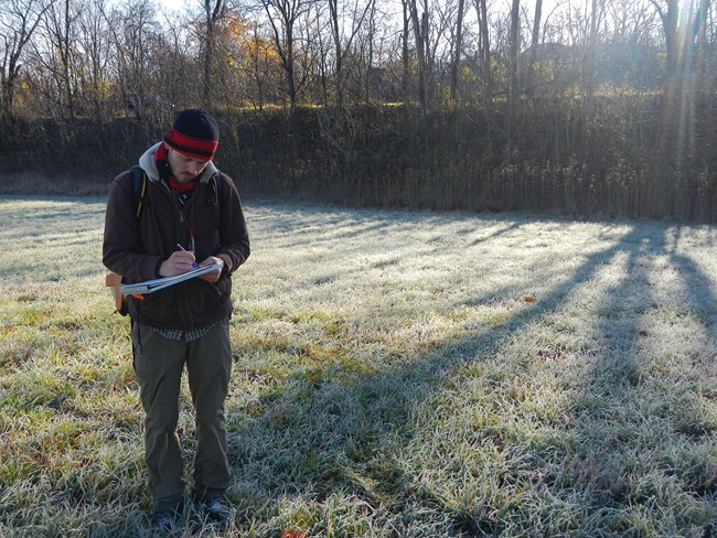 Standing in a frosty field, a man records landscape surroundings
