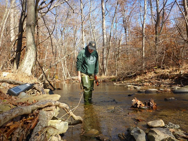 Person standing in creek with water quality monitoring gear